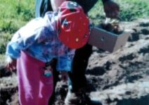Elyna and her Grandfather planting potatoes in the family garden