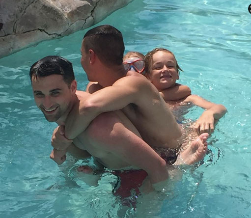 Caleb, Emma, and Ryan all trying to get a piggy back from Mark