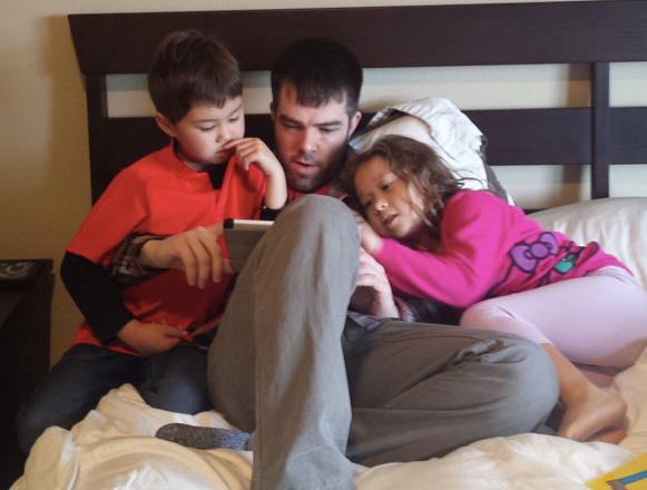 Uncle Kenneth reading to Eliza's niece and nephew, 2017