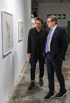 Tai showing the mayor John Tory around the Toronto Biennial, a show he co-curated in 2019.